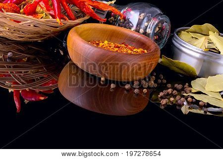Spices and herbs, bay leaf, red chili peppers, black peppercorn and wooden bowl of chili flakes on black background with reflection