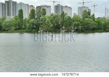 Man is engaged in wakeboarding on the background of construction