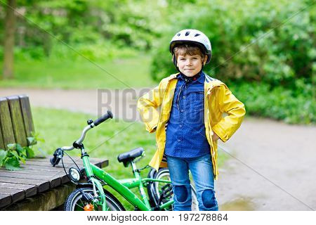 Cute little preschool kid boy riding on bicycle in park. Child in helmet, yellow rain coat and red rubber boots having fun on raine day on bike during rain
