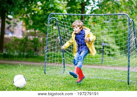 Active cute little kid boy playing soccer and football and having fun, outdoors. Child having game on rainy day. Wearing yellow rain coat and red rubber boots