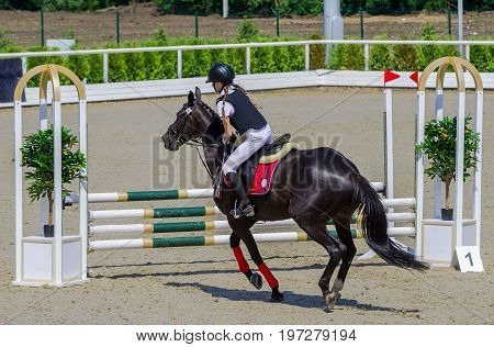 Young girl jumping with black horse. Blond pretty little girl going to jump a hurdle in a competition. Girl with horse during equestrian show jumping. Bright sunny day.