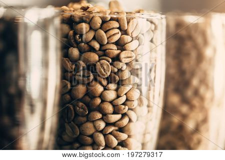Closeup Rosted Coffee Bean. Arabica Coffee Bean In Clear Glass Cafe Decoration.