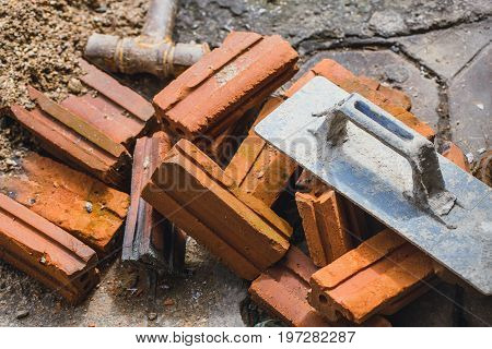 Construction Work Of Property Concept. Worker Tools With Brick In Dirty Workplace.