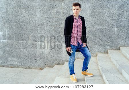 Stylish young man in plaid shirt and jeans walking up stairs and using smartphone outdoors. Student with smartphone walking up stairs free space