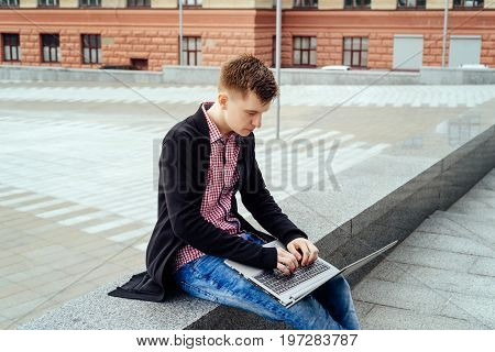 Stylish young man in jacket and jeans sitting and typing on laptop computer on knees outdoors free space. Technology and communication concept