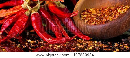 Red chili peppers and chili flakes on black banner background with reflection and copy space