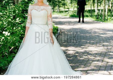 Beautiful Bride In Wedding Dress With Wedding Bouquet Of Peonies Waiting For The Groom In The Park O