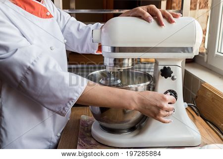 Young Woman Using Kitchen Mixer Preparing Dough For Bread Or Sweet Cake Cream
