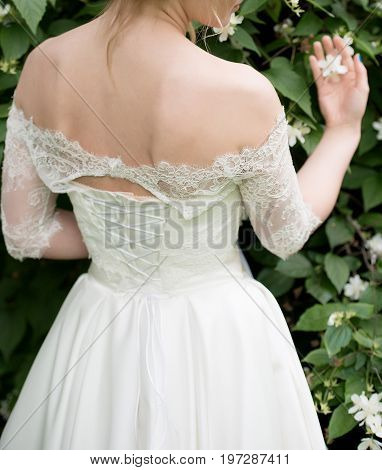 Beautiful Bride In White Dress With Naked Shoulders Standing Near Jasmine Bush And Holding One Jasmi