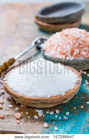 Two Different Types Of Natural Salt In Stone Bowls On Wooden Surface. White Sea Salt, Pink Himalayan