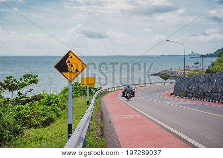 Yellow sign with beware of falling rocks symbol in the countryside sea and sky background .