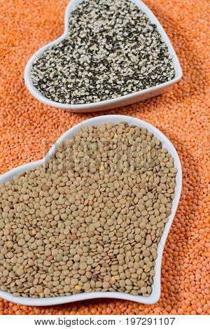Heart Form Bowls With Green And Black Lentils Over Red Lentils Background