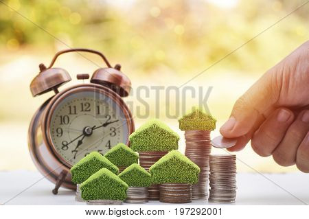 hand put money on stacked of coins to save for house small tree and home on pile with alarm clock on wood table with sunlight background concept as investment finance account and stock market