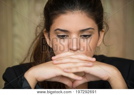 Close-up of face of young Caucasian businesswoman sitting in deep thought with clasped hands