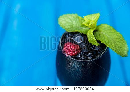 Close up glass with black cocktail garnished with mint and raspberry with blue wooden background