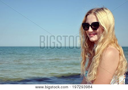 Girl with long hair and black sunglasses near the sea