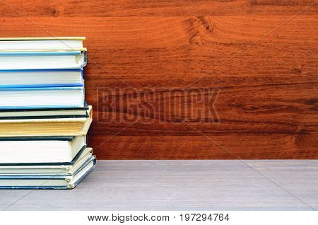 many books stacked close up photo with wood background