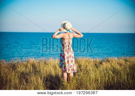 Summer Portrait Of Young Pretty Woman In A Straw Hat And Dress Standing Backwards In The Grass And L
