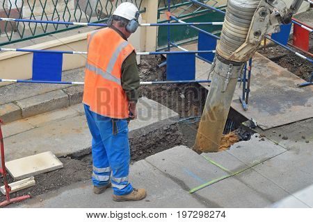 Asphalt worker controls the drilling process. Breaking concrete at road construction site