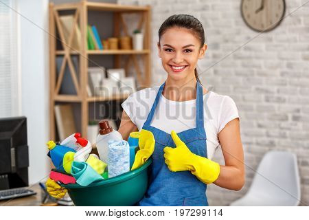 Studio shot of housekeeper. Beautiful woman cleaning office. Woman wearing gloves, smiling, showing thumb up and holding bowl full of bottles with disinfectant