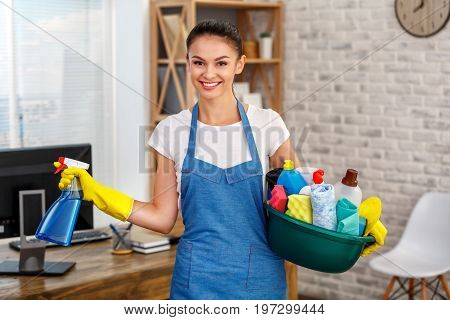 Studio shot of housekeeper. Beautiful woman cleaning office. Woman wearing gloves, smiling and holding bowl full of bottles with disinfectant