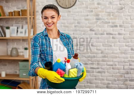 Studio shot of housekeeper. Beautiful woman cleaning room. Woman wearing gloves, smiling and holding bowl full of bottles with disinfectant