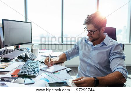 Entrepreneur writing notes sitting at his desk. Young man making business plans with papers and computers on his desk.