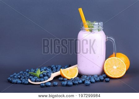 Close-up of a glass jar with bilberry smoothie on a dark blue background. A bunch of bilberries and cut oranges are near a full jar of bilberry drink with orange straw and decorative mint.