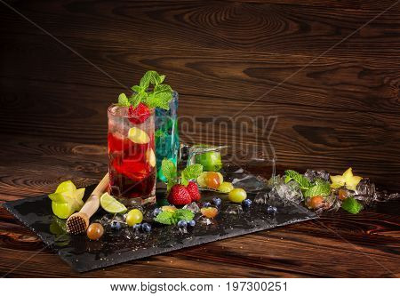 Beautiful bright cocktails with lime, strawberries, mint, bilberries, grapes, ice cubes and cocktail pounder on the black desk. Refreshing summer cocktails on the wooden background.