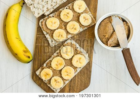 Healthy vegan homemade chunky peanut butter and banana sandwich with Swedish whole grain crispbread on wood cutting board spreading knife with spatula blade top view flat lay