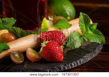 Close picture of colourful berries, lime, mint twigs and a pounder for cocktail ingredients on a black desk. Summer fruits on the wooden background. Tasty summer drinks with ripe fruits.