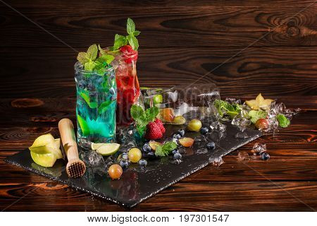 Blue and red beverages on a black desk. Refreshing bright cocktails in huge transparent glasses with mint, bilberries, strawberries, grapes, carambola and cocktail pounder on the wooden background.