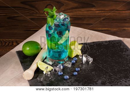 Close-up of blue fresh beverage on a black table-napkin and wooden background. Cool bright blue lagoon cocktail with lime segments, mint, bilberries, ice and carambola in huge glass. Summer beverages.
