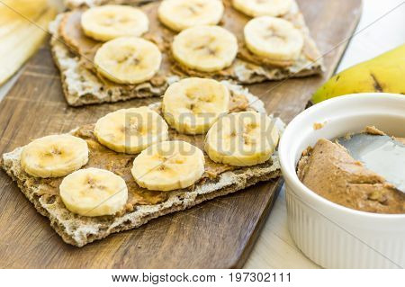 Healthy vegan dessert homemade peanut butter and banana sandwich with Swedish whole grain crispbread breakfast kitchen table wooden cutting board
