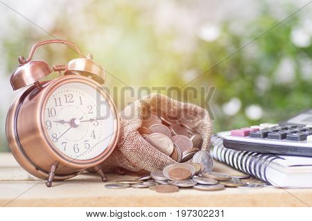 stacked of money and coins in sack alarm clock and calculator on wood table