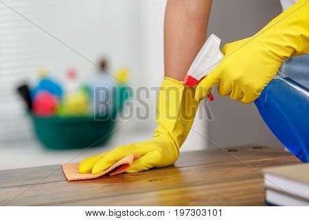 Close up studio shot of housekeeper. Beautiful woman cleaning table with spray. Woman wearing gloves. Focus on hands