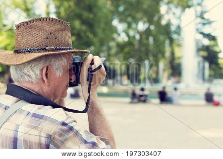 Senior pensioner tourist in hat photographing in vintage style in public city park