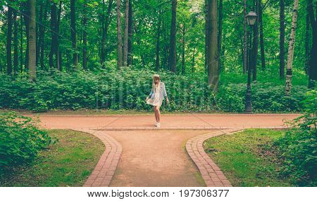 Portrait of pretty woman wearing dress and straw hat in summer warm weather day. Walking at summer park. Summer mood, ease of movement.