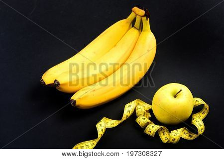 Bananas And Untwisted Measuring Tape Around Green Apple
