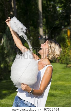 Girl eating sweet cotton candy in a summer park