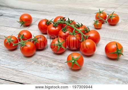 Cherry tomatoes lie on a wooden table. Horizontal photo.