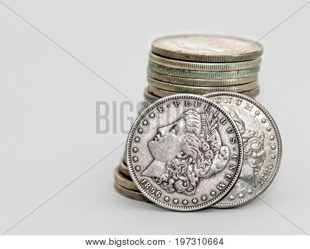 1896 and 1880 Morgan Dollar coins lean on a stack of other Morgans.
