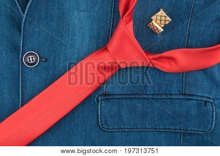 Red tie and cufflinks lie on the denim jacket. View from above