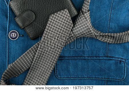 Grey tie and wallet lie on the denim jacket. View from above