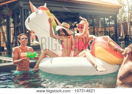 Group of friends in the swimming pool inflatable ring