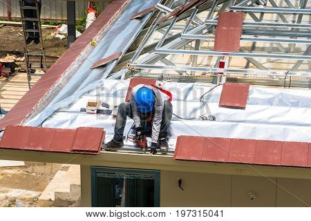 Workers are drilling roof tiles with a drill.
