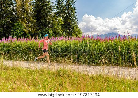 Woman athlete trail running in mountains on summer sunny day. Female athlete trail runner on country road. Sport and fitness concept outdoors in nature.