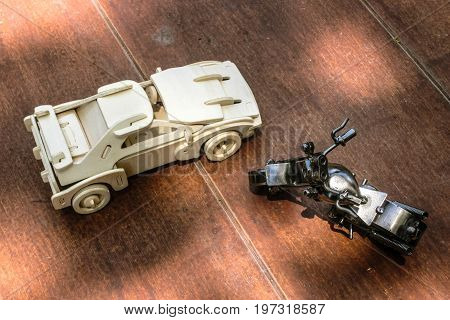 Top view of wooden car and steel chopper motorbike on wood floor.