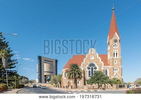 WINDHOEK NAMIBIA - JUNE 17 2017: A street scene with the Christuskirche an historic German Lutheran church and the Independence Memorial in Windhoek
