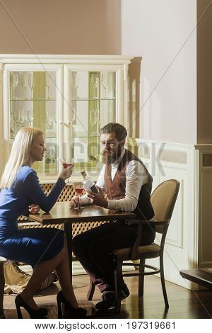 Man and woman dating in restaurant. Hipster and girl with blond hair drinking wine from martini glasses. Couple in love. Alcohol and appetizer. Addictive and convive. Unhealthy lifestyle. Bad habits